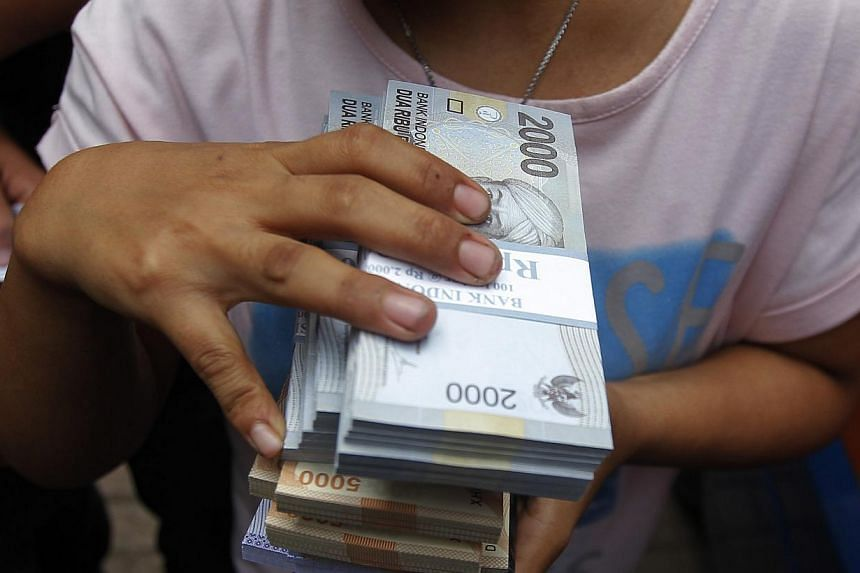 A woman holds Indonesian rupiah notes in Jakarta, on Dec 16, 2014.Indonesia's central bank unexpectedly cut its key interest rate by 25 basis points on Tuesday to spur growth as inflation slowed in Southeast Asia's biggest economy. -- PHO