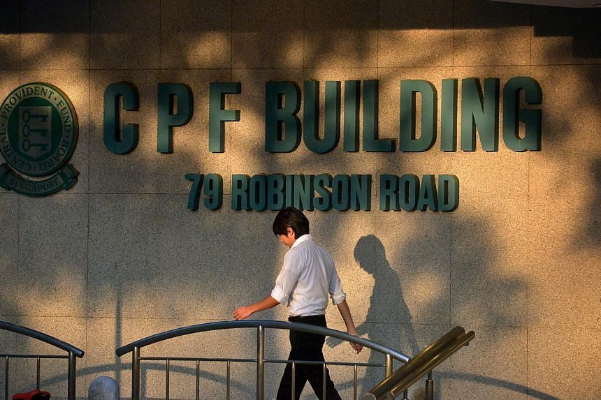 People walking past the CPF Building logo at the foot of the building along Robinson Road. -- PHOTO: ST FILE
