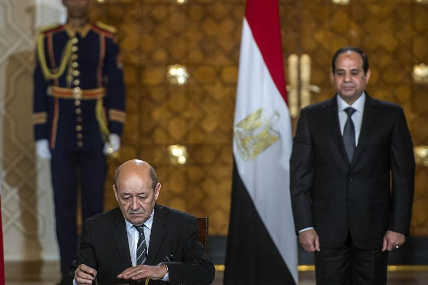 French Defence minister Jean-Yves Le Drian (left) signs military contracts with his Egyptian counterpart in the presence of Egyptian President Abdel Fattah al-Sisi (right) on Mondayat the presidential palace in the capital Cairo. Eric Trappier, chief
