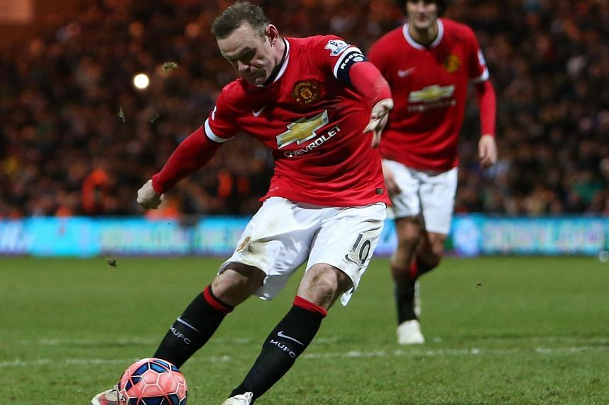 Manchester United's Wayne Rooney scores their third goal with a penalty. -- PHOTO: REUTERS