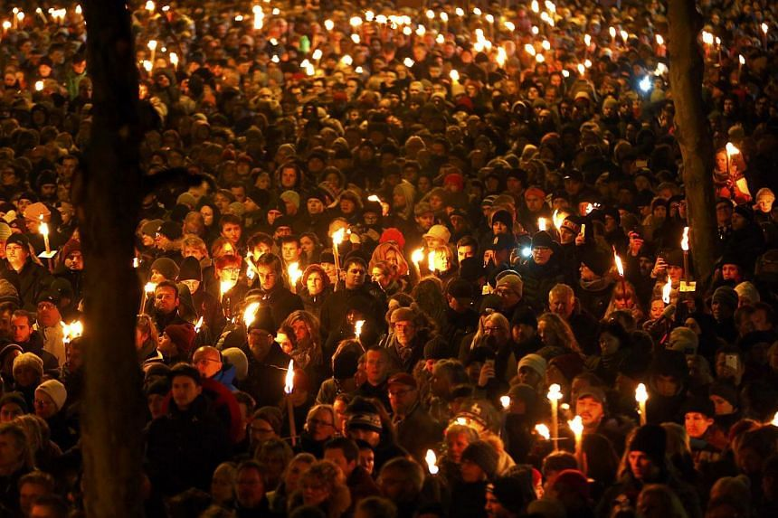 People hold candles during a memorial march on Monday for those killed on Saturday by a 22-year-old gunman in Copenhagen. -- PHOTO: REUTERS