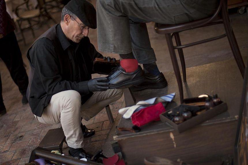 Spanish shoeshiner Javier Castano (left) shines shoes on Monday in Malaga. -- PHOTO: AFP