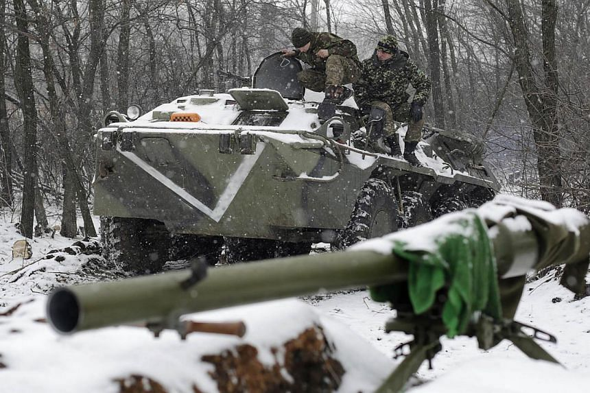 Ukrainian servicemen sit on an Armoured Personnel Carrier (APC) at a checkpoint near the town of Svitlodarsk, Donetsk region, on Monday. A two-day-old truce in Ukraine is under threat with fighting raging around a strategic railway hub, putting in pe