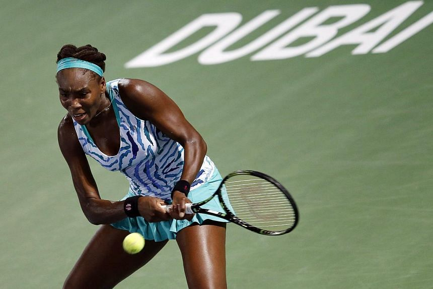 Venus Williams of the USA returns the ball to Belinda Bencic of Switzerland during their second round of the Dubai Duty Free Tennis WTA Championships in the United Arab Emirates on Monday. -- PHOTO: EPA