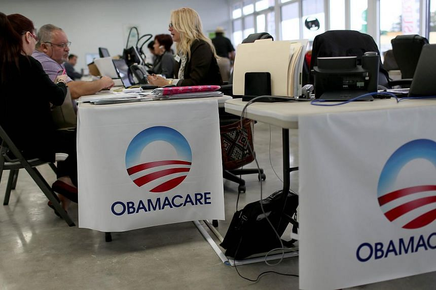Aymara Marchante (left) and Wiktor Garcia sit with Maria Elena Santa Coloma, an insurance advisor with UniVista Insurance company, as they sign up for the Affordable Care Act, also known as Obamacare, before the February 15th deadline on Feb 5, 2015