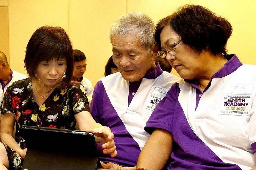 Senior Minister of State, Ministry of Health and Ministry of Manpower, Dr Amy Khor Lean Suan (left) showing Yong Poo Siyong (centre) and Koh Wei Choo, how to use Facebook on the iPad. -- ST PHOTO: CHEW SENG KIM