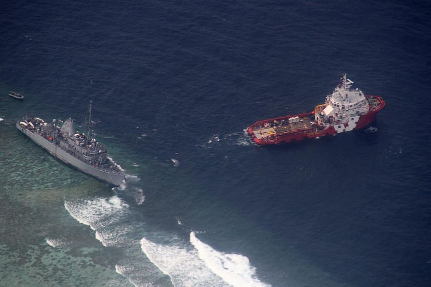 A Jan 24, 2013 photo shows an aerial view of the Malaysian tug boat Vos Apollo (right) preparing to remove fuel and other equipment from the US Navy ship USS Guardian (left), which ran aground in the vicinity of Tubbataha Reef, western Philippines. -