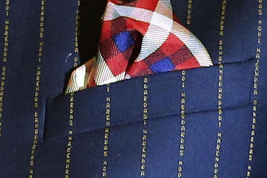 "A close-up view of Indian Prime Minister Narenda Modi's dark pinstripe suit, repeatedly embroidered with the words ""Narendra Damodardas Modi"". -- PHOTO: REUTERS"