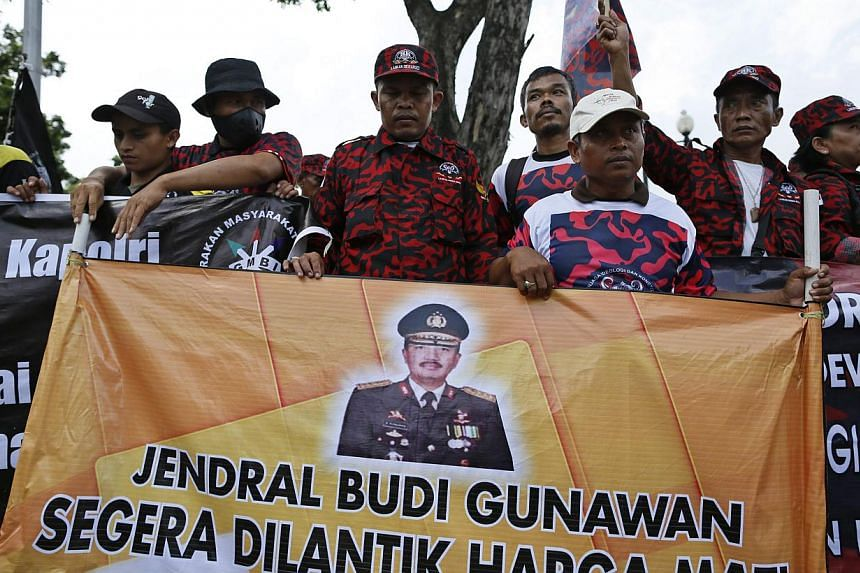 Supporters of Indonesian police chief nominee Budi Gunawan holding a banner with his picture outside the presidential palace in Jakarta, Indonesia on Feb 16, 2015, shortly after an Indonesian court cleared the three star general of being a graft