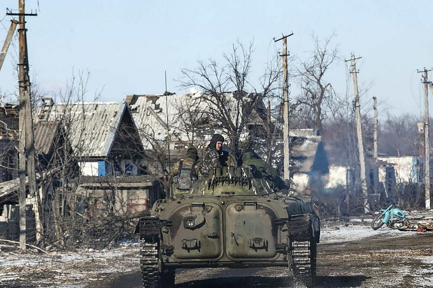 Fighters with separatist self-proclaimed Donetsk People's Republic army ride atop a moving armoured personnel carrier in the village of Nikishine, south east of Debaltseve on Feb 17, 2015. Pro-government forces began on Wednesday to pull out of the t