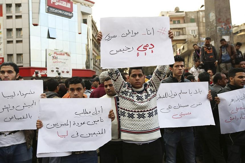 Egyptian Christians hold placards during a protest against the killing of Egyptian Coptic Christians by militants in Libya associated with the Islamic State in Iraq and Syria (ISIS), in Cairo on Feb 16, 2015. -- PHOTO: REUTERS