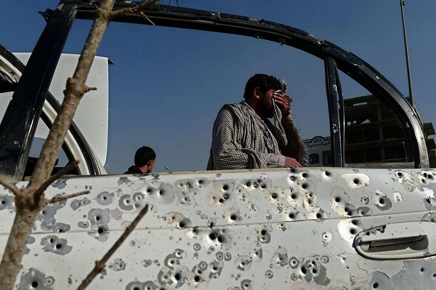 An Afghan pedestrian walks past a shrapnel-riddled car door following an explosion from a magnetic bomb attached to a civilian car in Kabul on Oct 14, 2014. The number of civilians killed and wounded in Afghanistan jumped 22 per cent in 2014, the UN