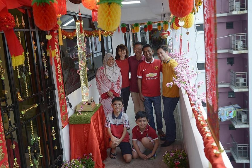 When Mr Pang Wei Ling (centre) first started his household decorations 13 years ago, they consisted of simple items like wall hangings and paper couplets. Today, the humble project has tripled in cost to about $300 and expanded into a massive array o