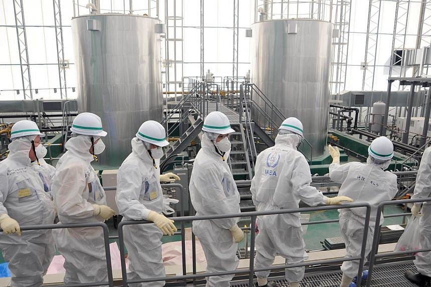 This handout picture released by International Atomic Energy Agency (IAEA) on Feb 17, 2015, shows IAEA mission team members inspecting TEPCO's Fukushima Daiichi Nuclear Power Station in Okuma, Fukushima prefecture. International advisers to Japa