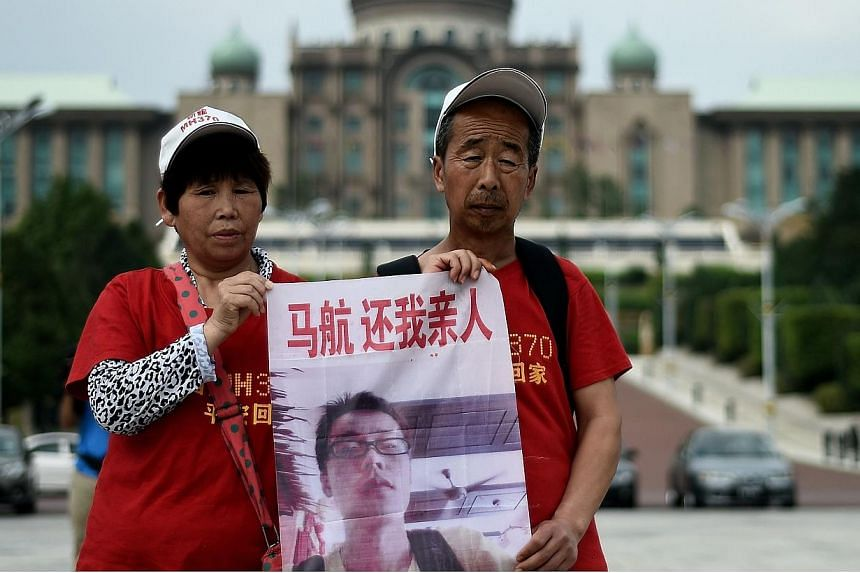 Relatives of Chinese passengers from the missing Malaysia Airlines flight MH370 gather outside Malaysian Prime Minister Najib Razak's office in Putrajaya on Feb 18, 2015. -- PHOTO: AFP