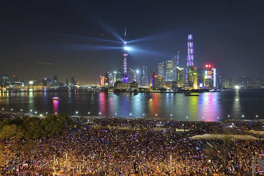 People watch a light show before a stampede incident occurred at the New Year's celebration on the Bund, a waterfront area in central Shanghai Dec 31, 2014. Shanghai is toning down Chinese New Year celebrations by cancelling events and limiting peopl
