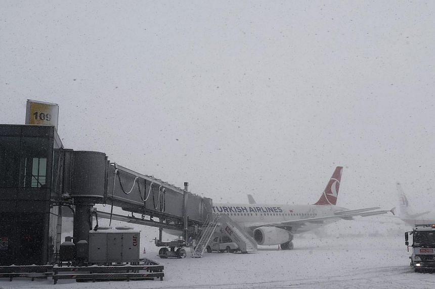 Planes stand on a parking area at Ataturk Airport during a snowy day in Istanbul, Turkey on Feb 18, 2015. A heavy fall of snow on Wednesday caused travel chaos in Istanbul, forcing the temporary closure of Turkey's main airport and causing hundreds o