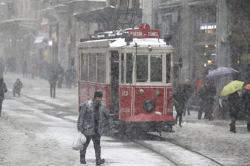 People walk during a snowy day in Istanbul, Turkey on Feb 18, 2015. -- PHOTO: EPA