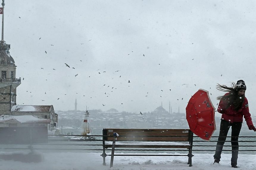 A woman with an umbrella pounded by the wind as she walks near Bosphorus during a snowy day in Istanbul, Turkey on Feb 18, 2015. -- PHOTO: EPA