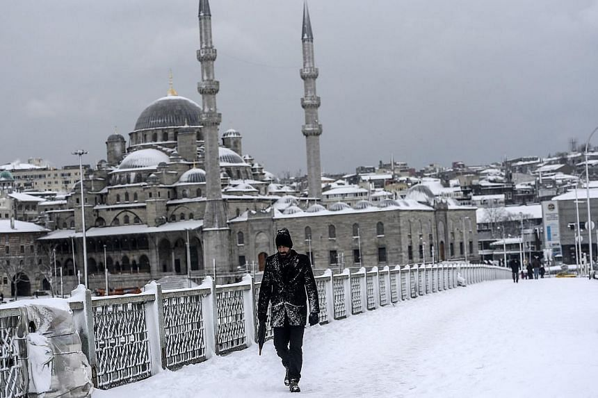 A man walks on the Galata bridge under heavy snow in the European side of Istanbul on Feb 18, 2015. -- PHOTO: AFP