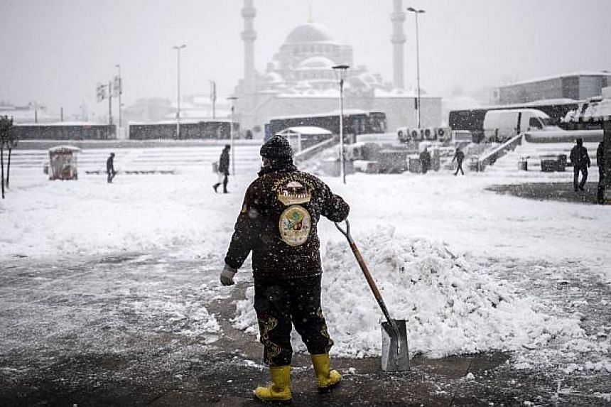 A man holds a shovel as he tries to clear a street during heavy snowfall in the European side of Istanbul on Feb 18, 2015. -- PHOTO: AFP