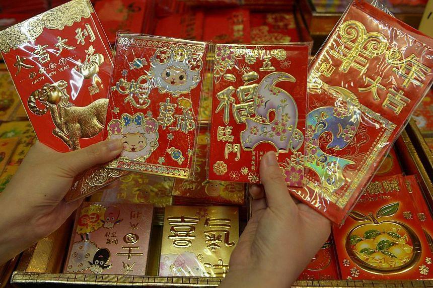 The Chinese tradition of giving gifts of money in red envelopes during the Lunar New Year has turned into big business for Web giants Alibaba and Tencent, which now both offer electronic hongbao. -- PHOTO: ST FILE