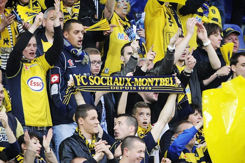 """Sochaux-Montbeliard 's football team supporters holding a scarf reading """"FC Sochaux Montbeliard, since 1928"""" during a football match between Sochaux and Evian at the Auguste Bonal stadium in Montbeliard last year.-- PHOTO: AFP"""