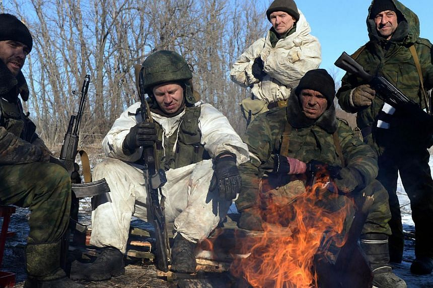 Pro-Russian rebels warm themselves by a fire during a break between fighting near the eastern Ukrainian city of Debaltseve on Feb 17, 2015. -- PHOTO: AFP