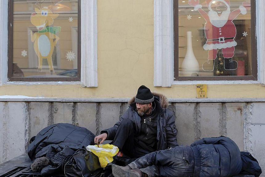 """Homeless men warm themselves on a ventilation outlet under windows with festive decorations in Moscow on Dec 30, 2014.A Russian couple allegedly carried out a string of murders targeting homeless people in Moscow to """"clean up"""" the city, investi"""