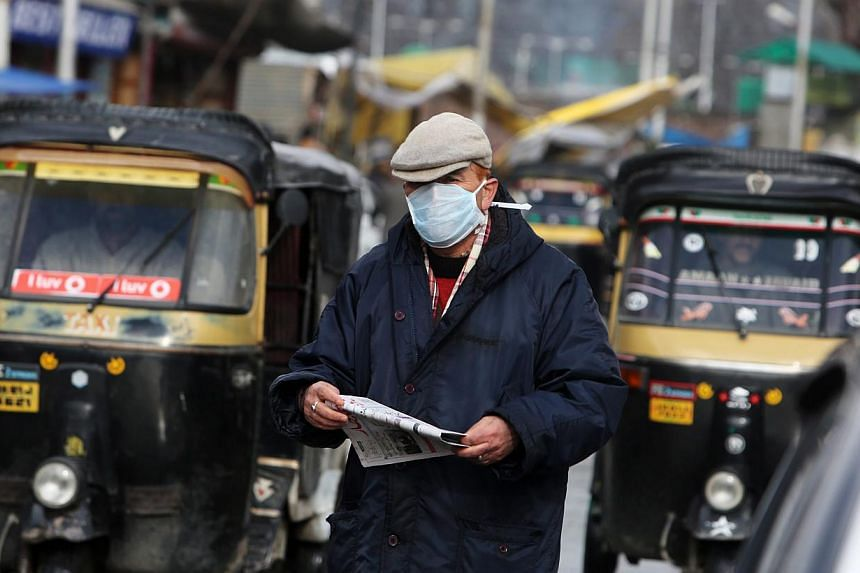 A Kashmiri man wearing a mask walks on a busy street in Srinagar, the summer capital of Indian Kashmir on Feb 18, 2015. India is urging its states to ensure sufficient supply of anti-flu medication and diagnostic tests as it struggles to curb an outb