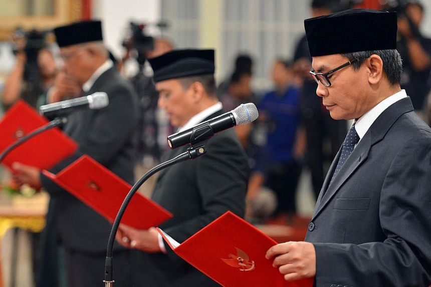 (From right) Johan Budi, Indriyanto Seno Aji and Taufiequrahman Ruki taking their oath before President Joko Widodo (not seen) during a ceremony at the presidential palace in Jakarta on Feb 20, 2015. -- PHOTO: AFP