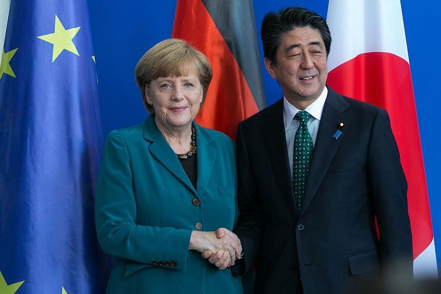 Japan's Prime Minister Shinzo Abe (right) and German Chancellor Angela Merkel after a news conference at the Chancellery in Berlin, Germany, on April 30, 2014. -- PHOTO: BLOOMBERG