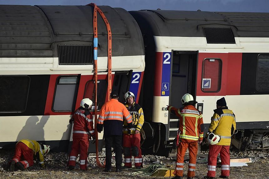 Firefighters inspect the site of a train crash at the train station of Rafz, northern Switzerland, on Feb 20, 2015. Two trains slammed into each other north of Zurich early on Friday, leaving passengers injured, Swiss police said. -- PHOTO: AFP