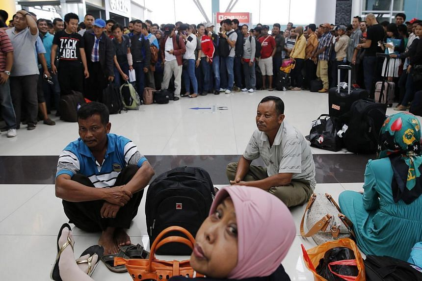 Lion Air passengers stand in a line to claim their tickets money back after their flights were delayed at Soekarno-Hatta airport in Jakarta on Feb 20, 2015. -- PHOTO: REUTERS