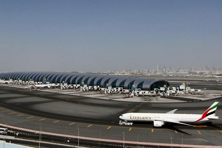 A plane passes next to the Emirates Airlines terminal at the concourse in Dubai International Airport, Jan 7, 2013.An increasingly bitter trade row between US and Gulf airlines deepened on Thursday when Dubai's Emirates rejected a Delta A