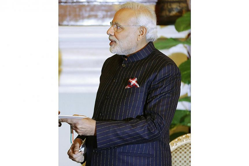 """Indian Prime Minister Narenda Modi, wearing a dark pinstripe suit repeatedly embroidered with the words """"Narendra Damodardas Modi"""", meets with US President Barack Obama at Hyderabad House in New Delhi on Jan 25, 2015.A diamond trader from Mr Mo"""