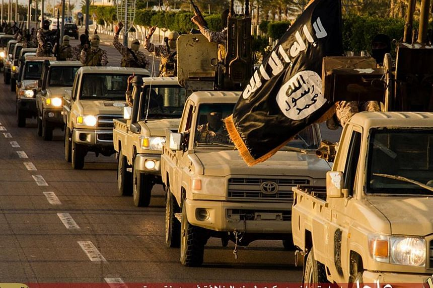 An image made available by propaganda Islamist media outlet Welayat Tarablos on Feb 18, 2015, allegedly shows ISIS militants parading in a street in Libya's coastal city of Sirte, which lies some 500km east of the capital, Tripoli. -- PHOTO: AFP