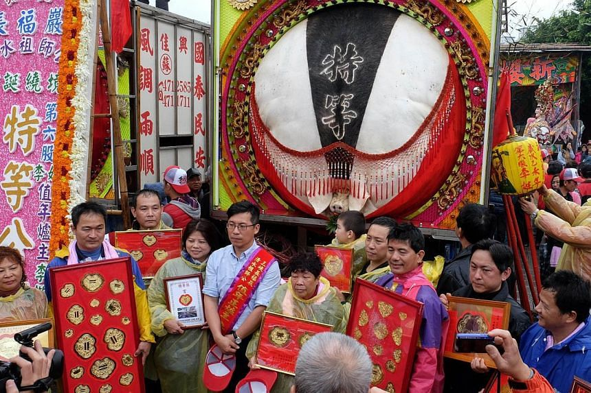 """Lee family members posing for photos in front of a pig weighing 714.6kg during the annual """"Holy Pigs"""" Festival outside the Zushi Temple in Shanhsia district, New Taipei City on Feb 24, 2015. -- PHOTO: AFP"""