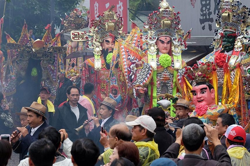 """Taoist gods are surrounded by local residents during the annual """"Holy Pigs"""" Festival outside the Zushi Temple in Shanhsia district in New Taipei City on Feb 24, 2015. -- PHOTO: AFP"""