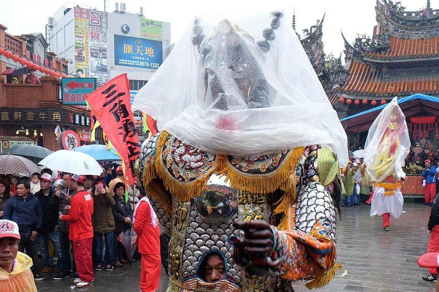 """A man dressed in a Taoist god costume attending the annual """"Holy Pigs"""" Festival outside the Zushi Temple in Shanhsia district, New Taipei City on Feb 24, 2015. -- PHOTO: AFP"""