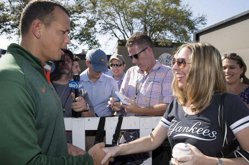 New York Yankees' Alex Rodriguez (L) greets a fan waiting for a autograph at the Yankees minor league complex for spring training in Tampa, Florida on Feb 23, 2015. -- PHOTO: REUTERS