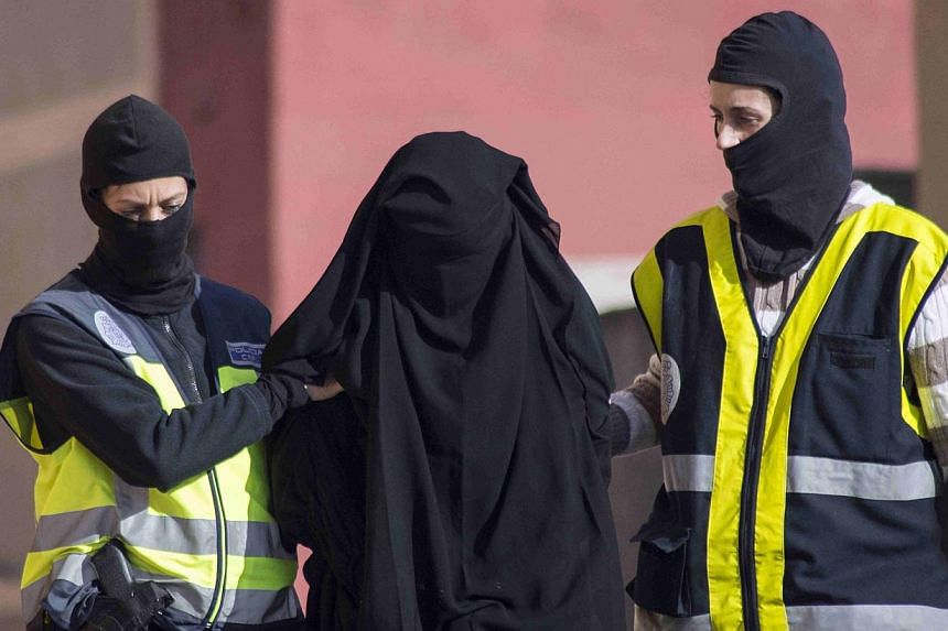 Masked Spanish police officers lead a detained woman in Melilla on Dec 16, 2014. Spain said on Tuesday it had broken up an online network accused of recruiting young women to join the Islamic State in Iraq and Syria (ISIS) and arrested four susp