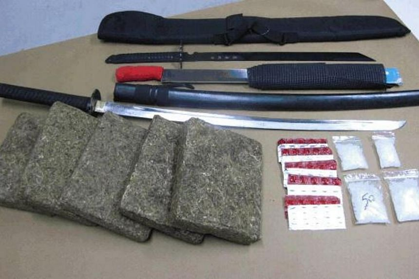 Drugs and weapons seized in the CNB operation in Geylang on Feb 23, 2015. -- PHOTO: CNB