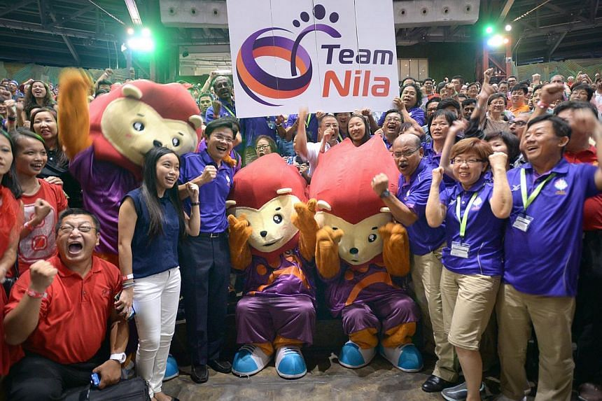 Minister for Community, Culture and Youth Lawrence Wong with volunteers for the 28th SEA Games and Games mascot Nila at Universal Studios on Feb 24, 2015.-- ST PHOTO: LIM SIN THAI