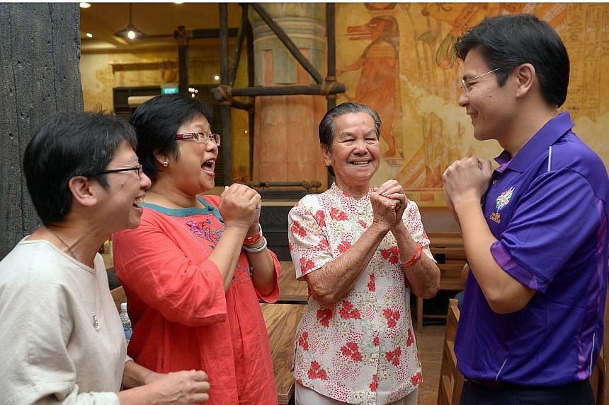 Minister for Community, Culture and Youth Lawrence Wong greeting three volunteers of the 28th SEA Games to be held in Singapore, from second right, Mdm Seah Wai Ying, 84, Ms Choo Bee Leng, 51 and Mdm Seah's daughter, Ms Lim Lea Cheen, 53. -- ST PHOTO