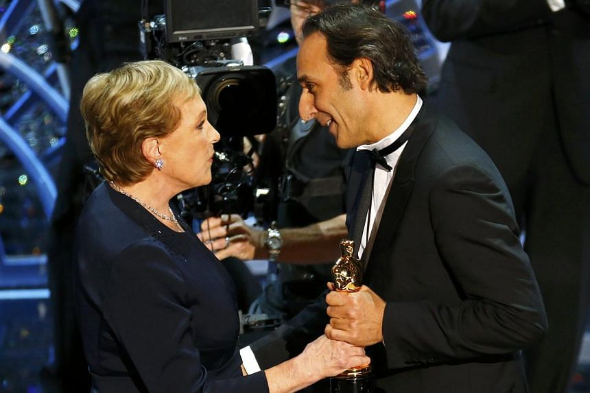 Birdman's (above from left) James W. Skotchdopole, Alejandro Gonzalez Inarritu and John Lesher with their Best Picture Oscars; Julie Andrews giving Alexandre Desplat his trophy for Best Original Score for the film, The Grand Budapest Hotel; and (belo
