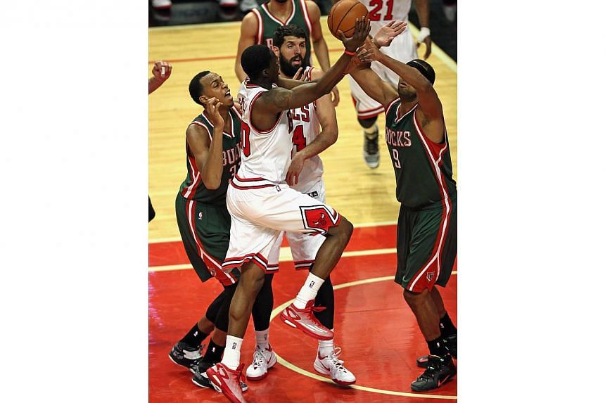 Tony Snell (centre) of the Chicago Bulls drives to the basket between John Henson (left) and Jared Dudley (right) of the Milwaukee Bucks on his way to a game-high 20 points at the United Center on Feb 23, 2015 in Chicago, Illinois. -- PHOTO: AFP