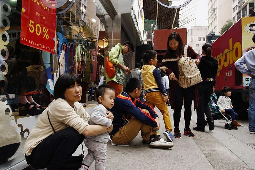 Mainland Chinese visitors rest outside a shop at a shopping district in Hong Kong on Feb 24, 2015. -- PHOTO: REUTERS