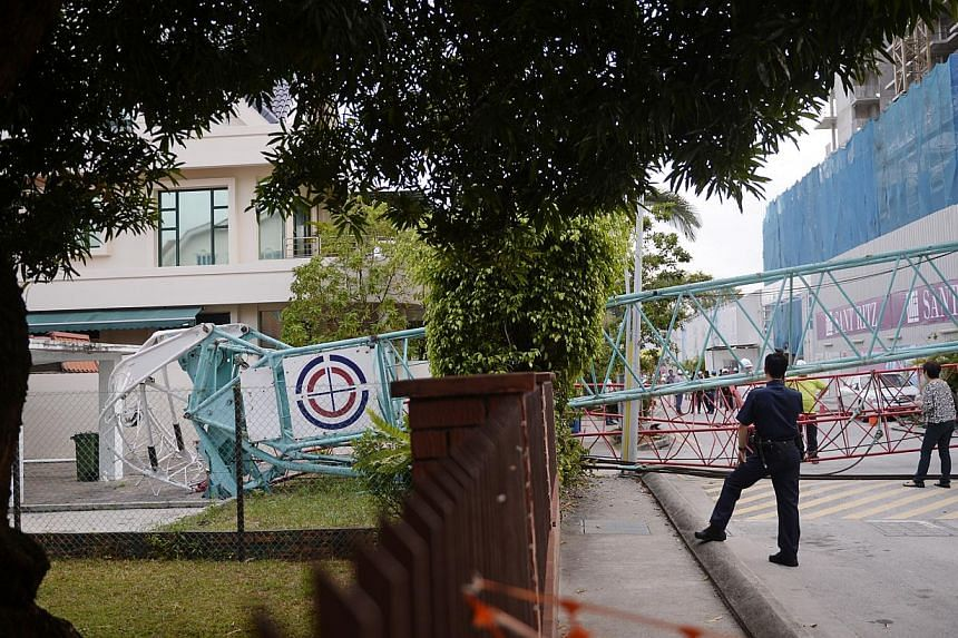 A crane from the construction site of upcoming condo Sant Ritz, in Potong Pasir, toppled over on Tuesday and crashed into the front yard of a semi-detached house across the road. -- ST PHOTO: MARK CHEONG