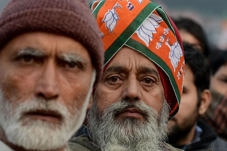 Kashmiri supporters of Indian Prime Minister Narendra Modi look on as he speaks during an election rally at a stadium in Srinagar on Dec 8, 2014. Prime Minister Narendra Modi hit the campaign trail for regional elections in Indian Kashmir just days a